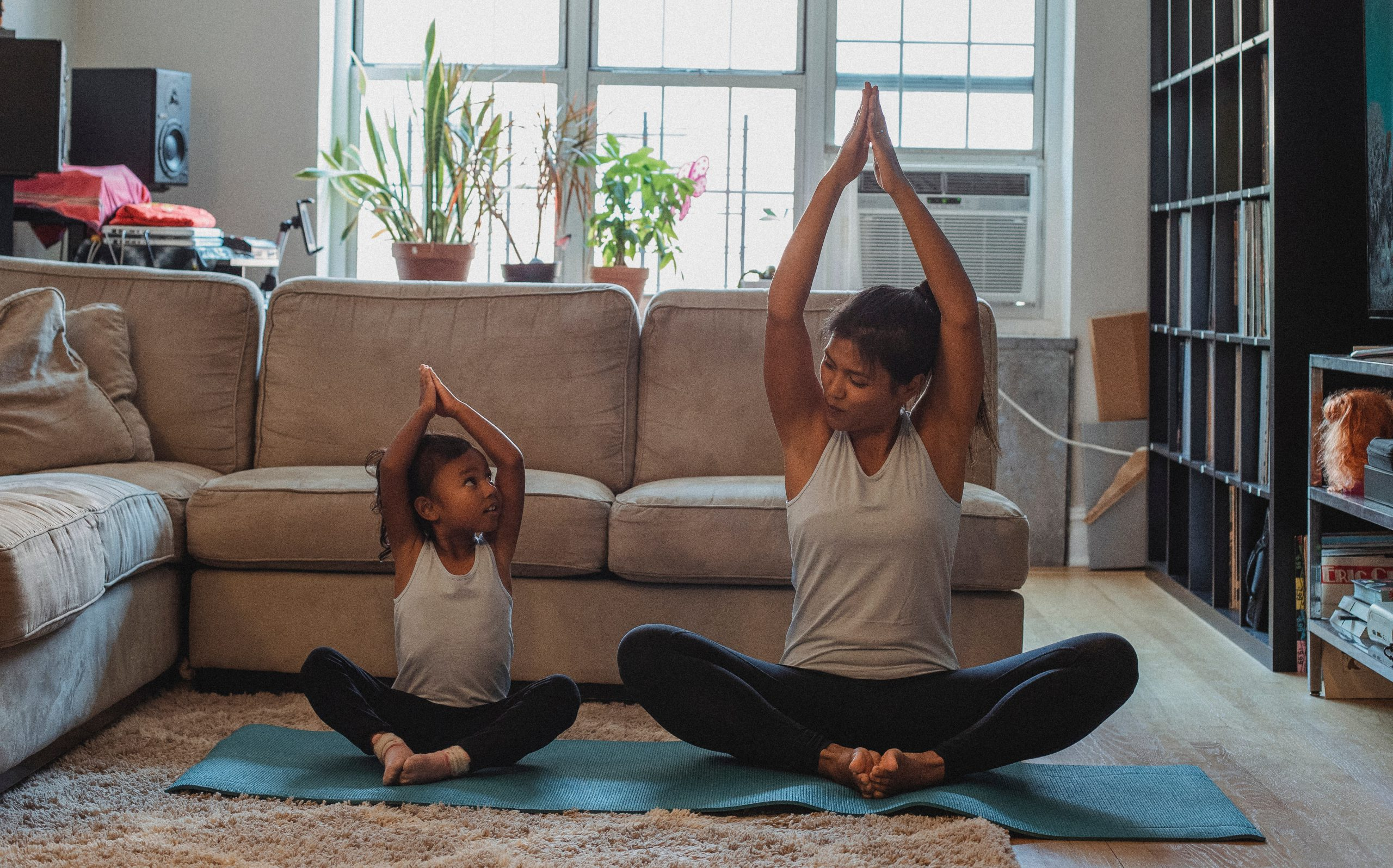 kid doing physical activity yoga with mother